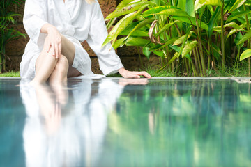 Woman resting at pool with feet in water.