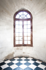 Grungy arched window inside old building.