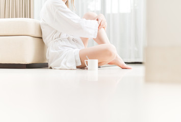 Woman in white bathrobe sitting on floor.
