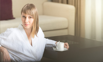 Woman in robe with coffee in hotel room.