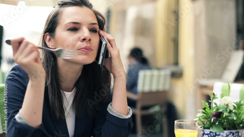Businesswoman talking on cellphone during lunch break in cafe