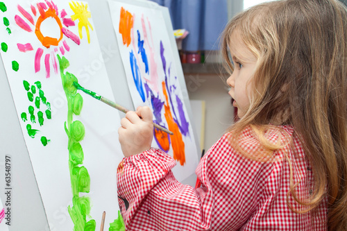 Little girl painting on paper