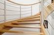 Leinwandbild Motiv Curved wooden staircase with stainless steel elements