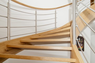 Curved wooden staircase with stainless steel elements