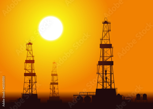 Oil rigs over sunset.