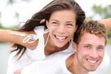 Happy couple on beach having fun piggyback in love