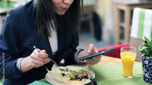 Businesswoman texting on smartphone during lunch in cafe