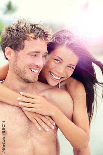 Happy romantic couple lovers on beach honeymoon
