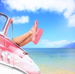 Woman legs by blue sea background in car