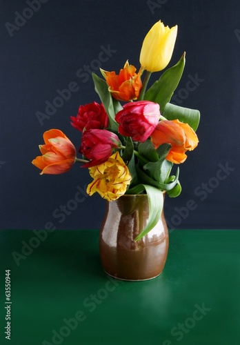 multicolor tulips in brown ceramic mug