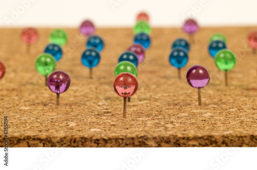 Brightly Colored Pushpins In Corkboard
