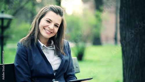 Happy attractive businesswoman with tablet computer in park