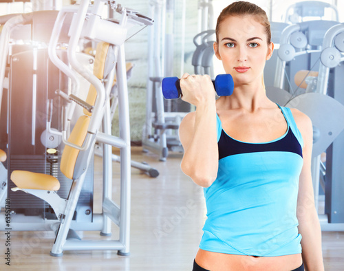 Sporty female doing physical exercise in gym