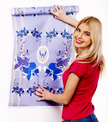Happy woman glues wallpaper .