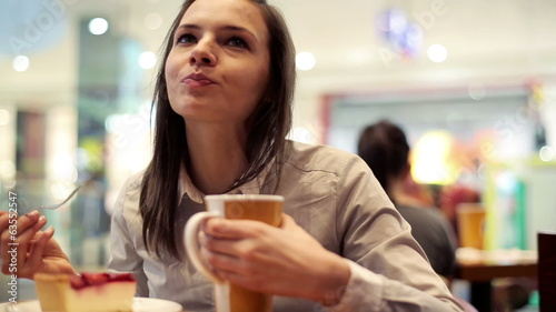 Woman eating delicious cake and drink coffee in cafe