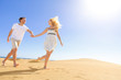 Couple holding hands running having fun under sun