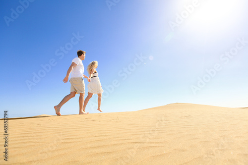 Couple running having fun holding hands under sun