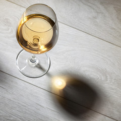 Glass of white wine on wooden table. Top view