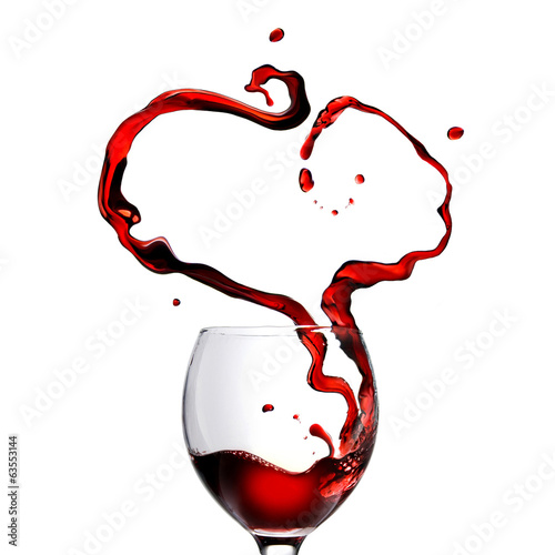 Heart made of pouring red wine in glass isolated on white