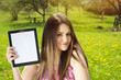 Beautiful young woman in park showing tablet computer