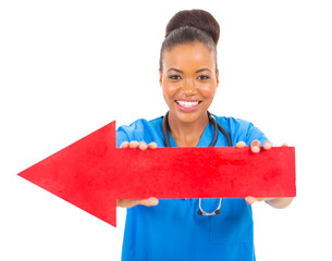african female doctor holding direction arrow