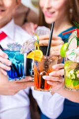 Cocktailgläser an Leuten in Bar beim Feiern
