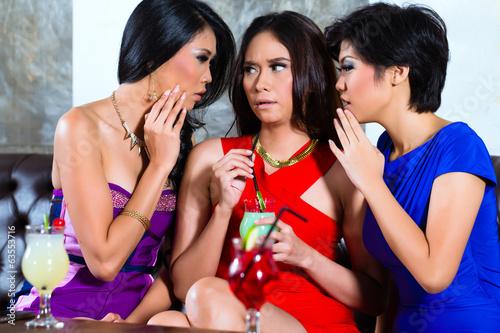 Asian friends gossiping in nightclub