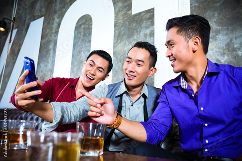 Asian friends taking pictures or selfies in fancy night club
