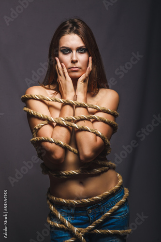 brunette hostage, captive bound woman with rope prisoner in jean