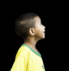 Brazilian little boy looks to the infinite on black background