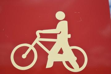 Simbolo de ciclista empujando una bicicleta a pie
