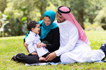muslim family sitting outdoors