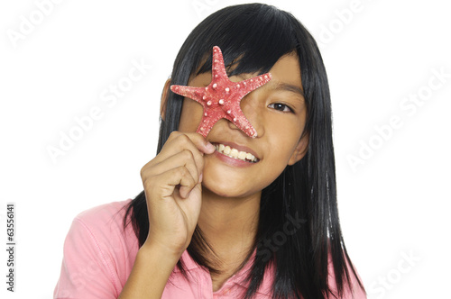 Asian little girl playing with starfish