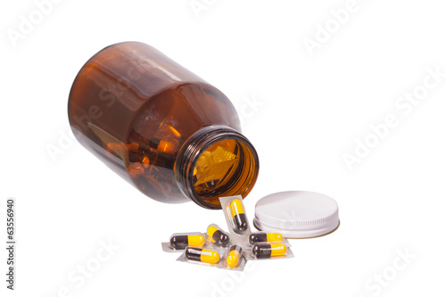 yellow and black capsules drug and bottle isolated on white