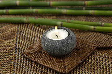 Thin bamboo and candle on straw mat