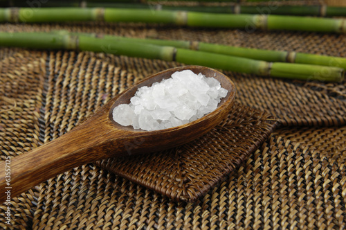 Salt in wooden spoon and bamboo grove on mat