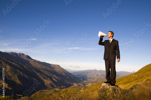 Businessman Shouting on the Top of the Mountain