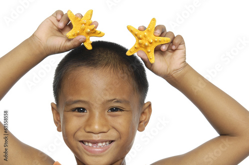 Little boy playing with starfish-closeup