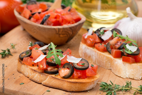 ciabatta with tomatoes, olives, parmesan on a wooden board