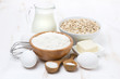 milk, cereal and ingredients for baking on white wooden table