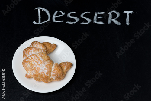fresh croissant on a plate on the blackboard