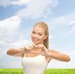 smiling woman showing heart shape gesture
