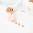 female hand putting euro coins into piggy bank