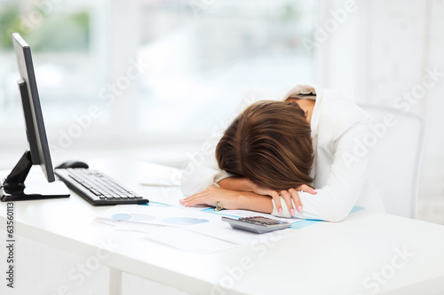 stressed woman with computer, papers, calculator
