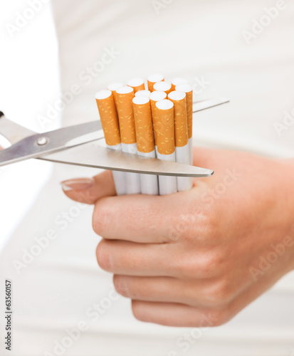 close up of scissors cutting many cigarettes