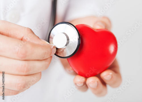 male hands holding red heart and stethoscope
