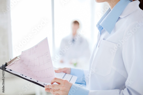 female holding clipboard with cardiogram