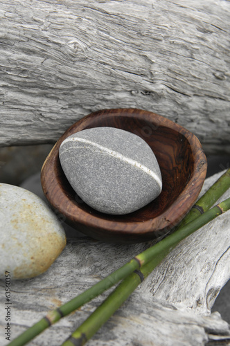 Spa rocks in wooden bowl with grove on rustic wood