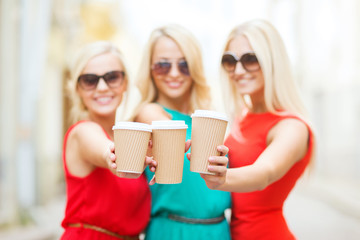 blonds holding takeaway coffee cups in the city