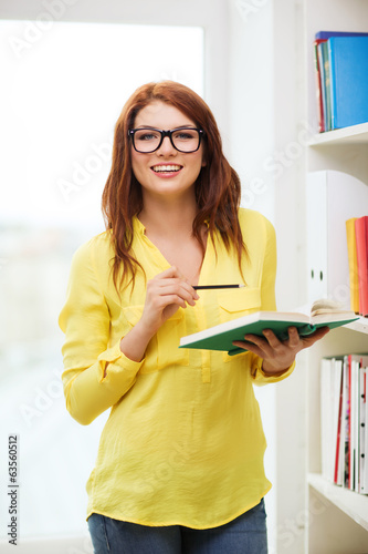 female student in eyeglasses with book and pencil